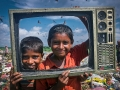 The Children at fun to front of Camera with waste TV frame. The poor Children pick sellable household materials and sell to market for their livelihood. The permanent Waste land under Sylhet City Corporation. Lalmatia, Sylhet, Bangladesh.