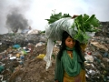 A girl back to home end of day with vegetable, she collected from waste land. The permanent Waste land under Sylhet city corporation. Lalmatia, Sylhet, Bangladesh.